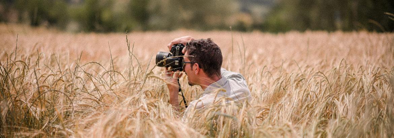 jeune homme avec son appareil dans les champs de blé